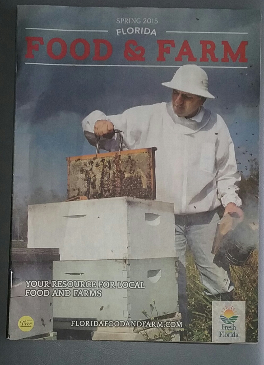 Food and farm magazene with Steve Byers pulling a bee frame out of a bee hive