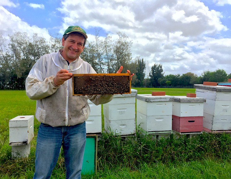 Steve Byers holds up a bee frame